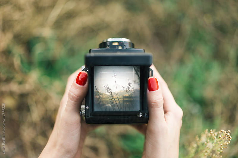 girl taking pictures with the vintage camera by Javier Pardina for Stocksy United
