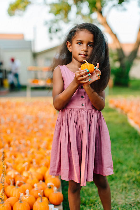 A young African American girl holding a mini pumpkin by Kristen Curette Hines for Stocksy United