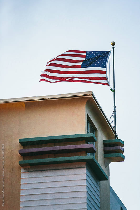 View of a an american flag flying in the wind on top of a building by Alejandro Moreno de Carlos for Stocksy United