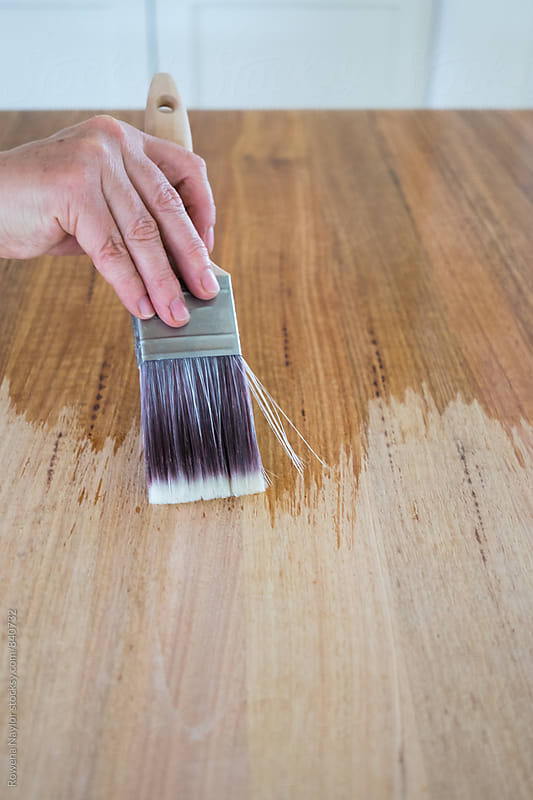 Home DIY, varnishing a kitchen bench by Rowena Naylor for Stocksy United