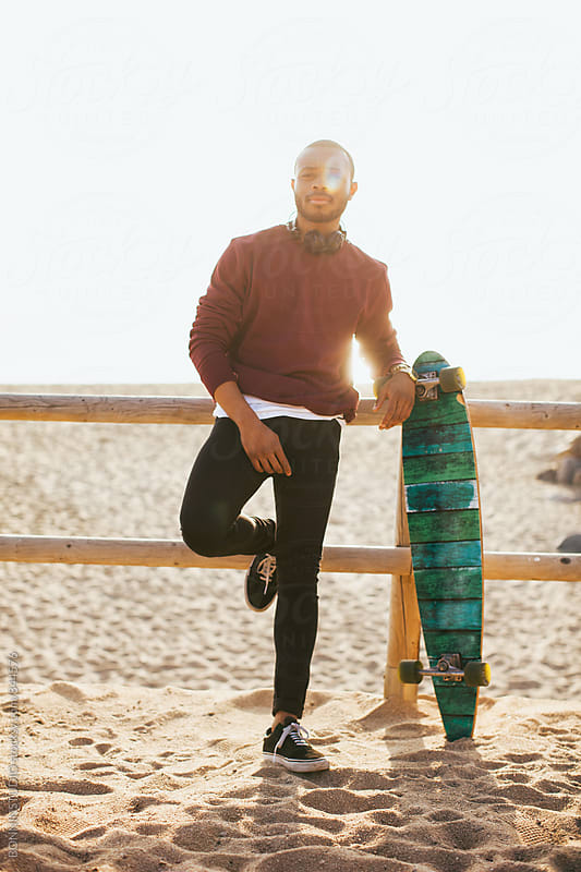 Young man standing with his longboard on the beach. by BONNINSTUDIO for Stocksy United