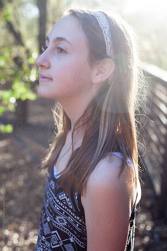 Profile of a young girl smiling and looking ahead by Carolyn Lagattuta for Stocksy United