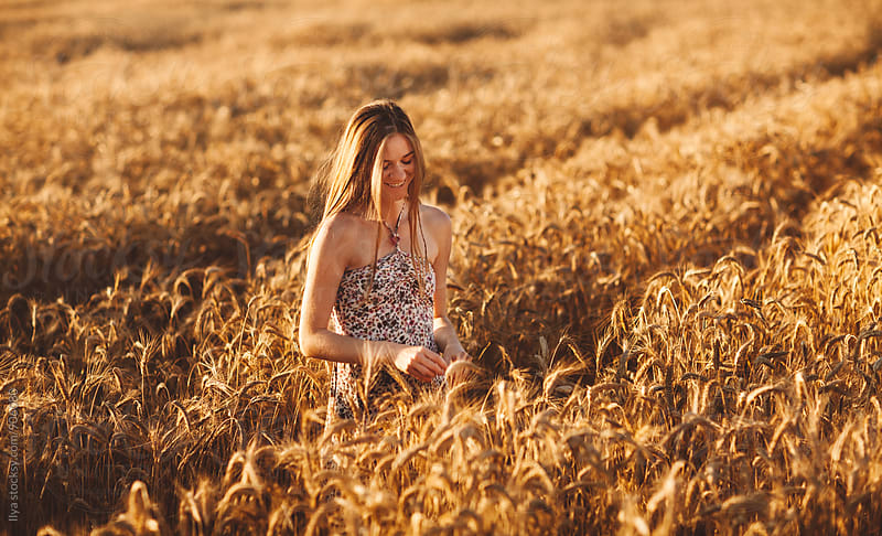 Young woman in summer dress smiling in wheat field by Ilya for Stocksy United