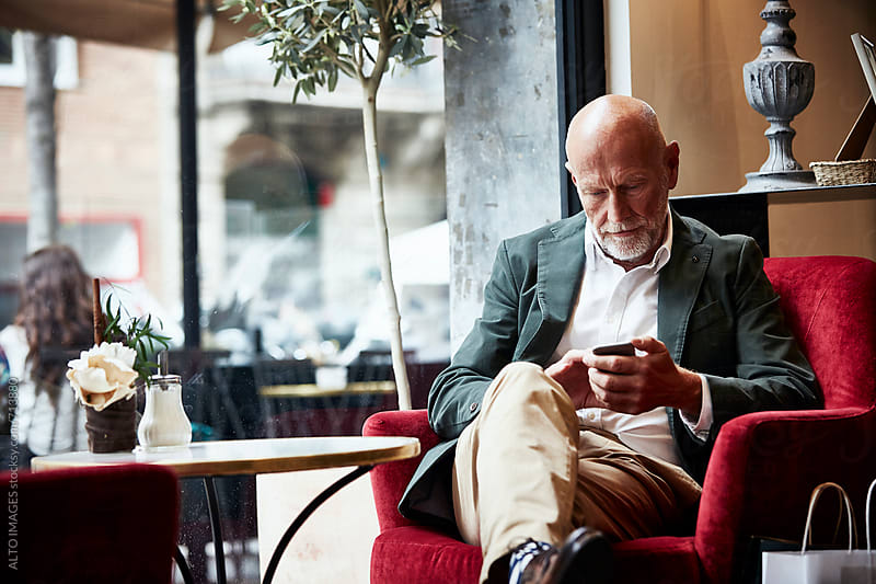 Senior Man Using Mobile Phone In Restaurant by ALTO IMAGES for Stocksy United