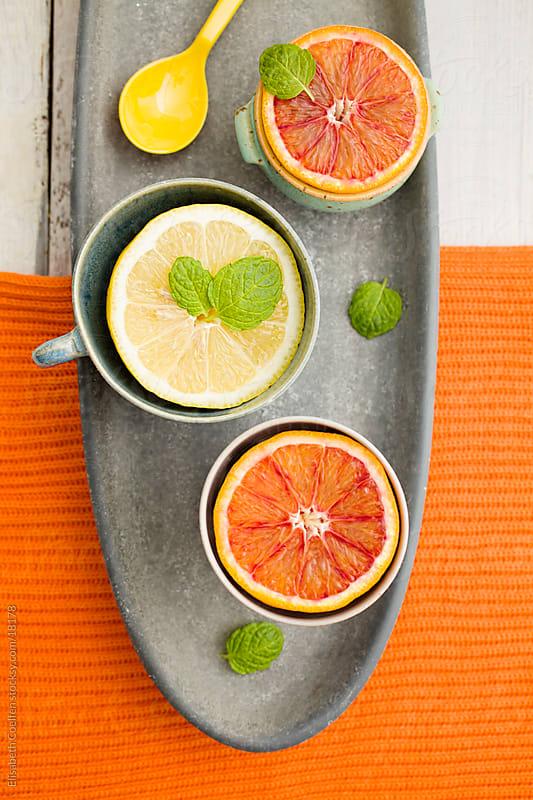 Blood orange and lemon halves in cups garnished with mint leaves on oval grey platter by Elisabeth Coelfen for Stocksy United