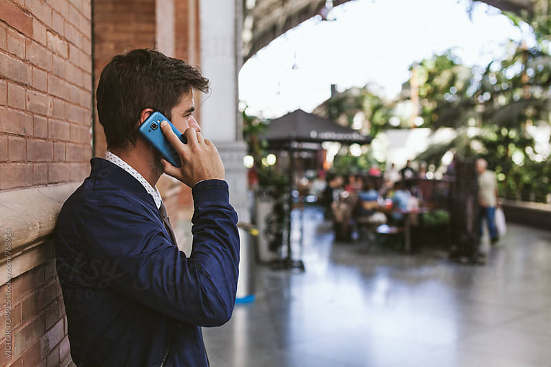 Elegant Young Businessman Talking by Phone by Victor Torres for Stocksy United