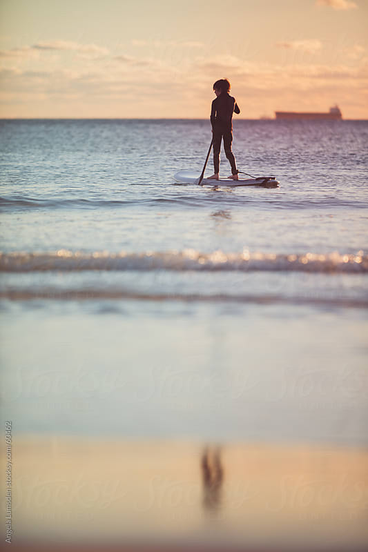 Small boy on a stand up paddle board at sunset by Angela Lumsden for Stocksy United