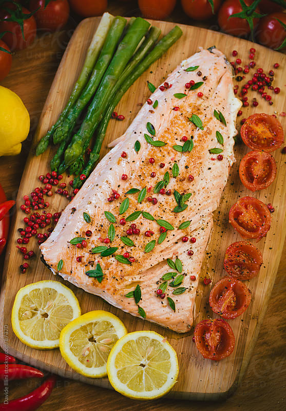 Fillet of salmon with asparagus and tomatoes by Davide Illini for Stocksy United