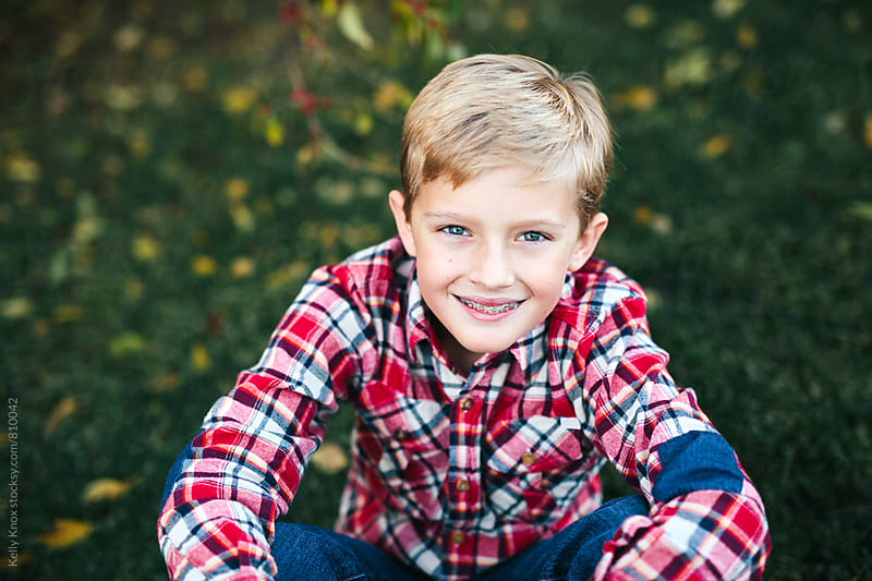 fall portrait of a smiling boy by Kelly Knox for Stocksy United