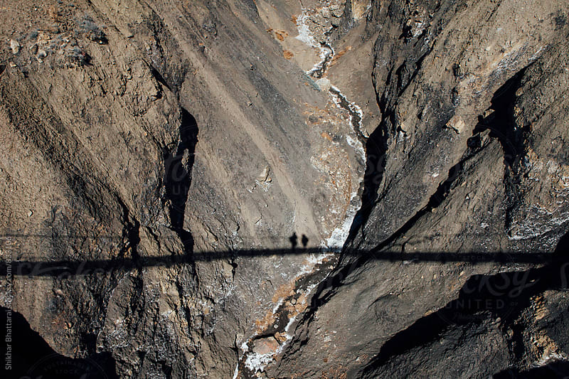 Shadow of two travellers on a suspension bridge looking down. by Shikhar Bhattarai for Stocksy United