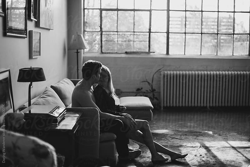Young couple sitting together hugging on couch in industrial loft by Daring Wanderer for Stocksy United