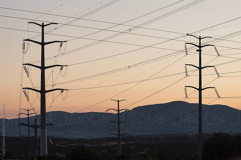 Electricity transmission line at dusk by Luis Cerdeira for Stocksy United