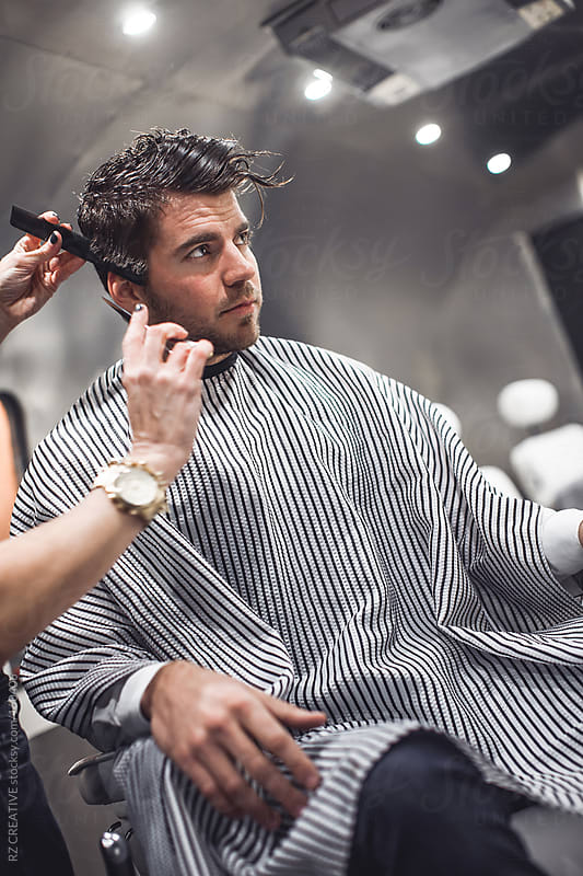 A young man at the barber. by Robert Zaleski for Stocksy United
