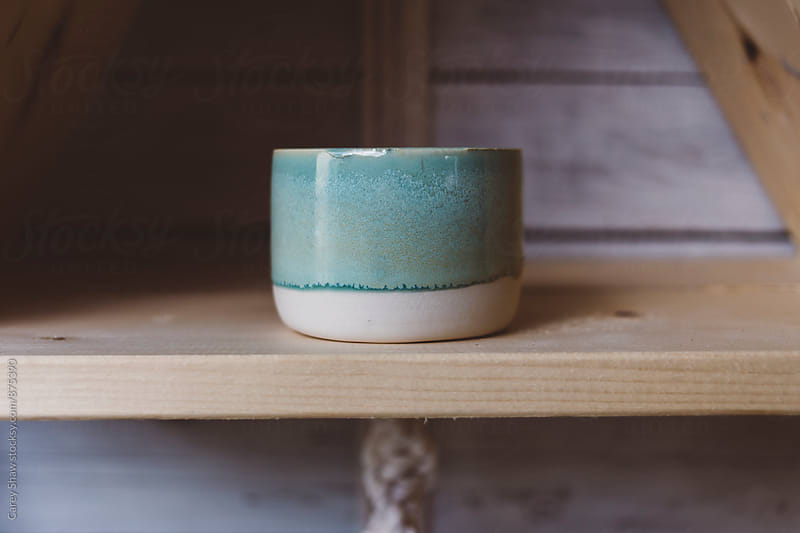 Handmade ceramic bowl on wood shelf by Carey Shaw for Stocksy United