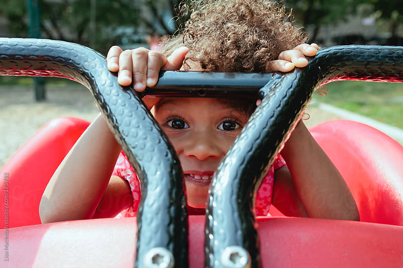afro american girl peeking between handlebars of ride at park by Lisa MacIntosh for Stocksy United