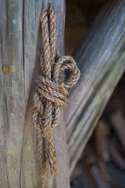 A rope knot hanging in a wood column by Leandro Crespi for Stocksy United