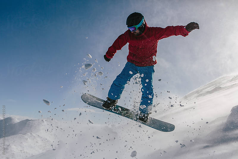 snowboarder jumping down the hill by Peter Meciar for Stocksy United