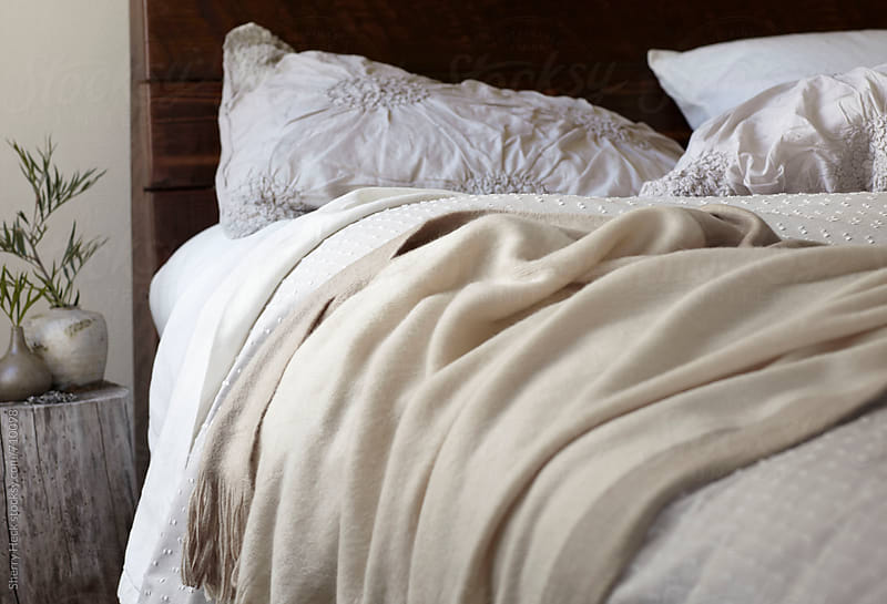 Half of a bed with beige linens with a wood stump night stand by Sherry Heck for Stocksy United