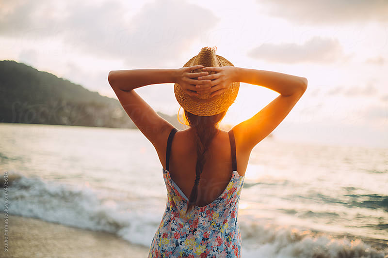 Young woman with hat watching sunset on the beach. by Studio Firma for Stocksy United