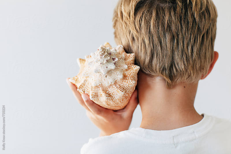 behind a child listening to a conch shell by Kelly Knox for Stocksy United