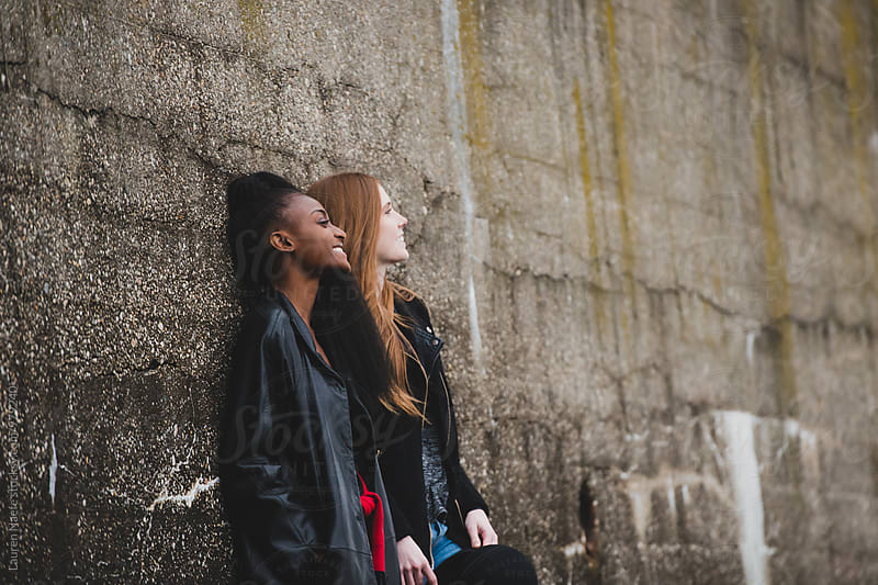 Two friends laughing and hanging out in the city by Lauren Naefe for Stocksy United