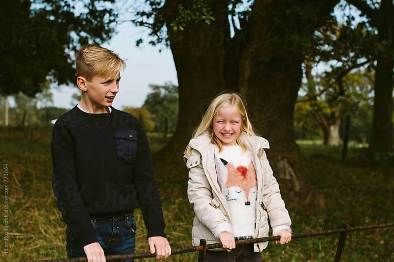 A brother and sister standing on a fence in the countryside. by Helen Rushbrook for Stocksy United