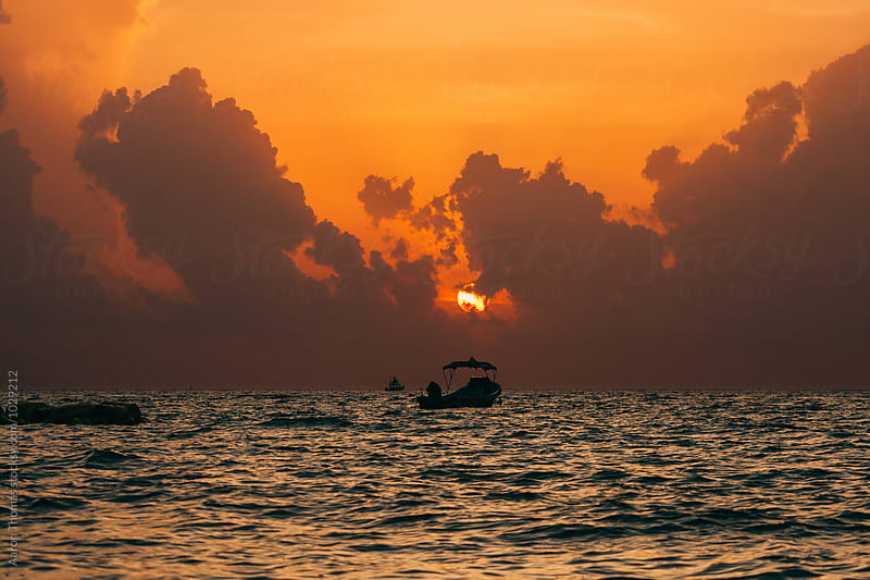 Fishing boat our during Sunrise in Playa del Carmen by Aaron Thomas for Stocksy United
