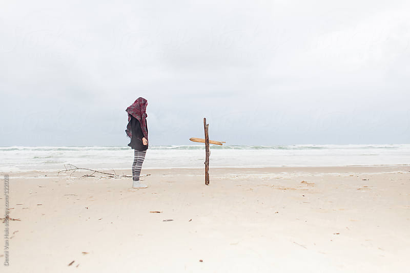 Sad woman standing next to a wooden cross on the beach. by Denni Van Huis for Stocksy United