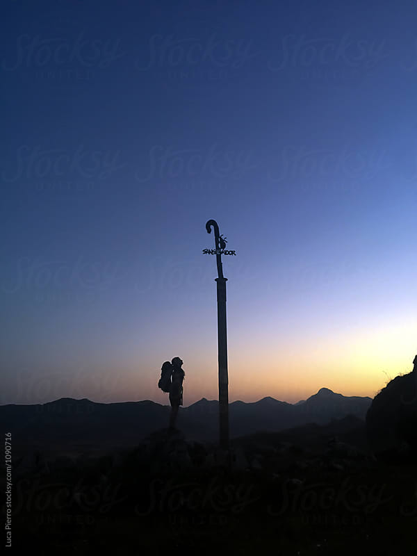 Hiker on the summit of a mountain looking at a cross  by Luca Pierro for Stocksy United