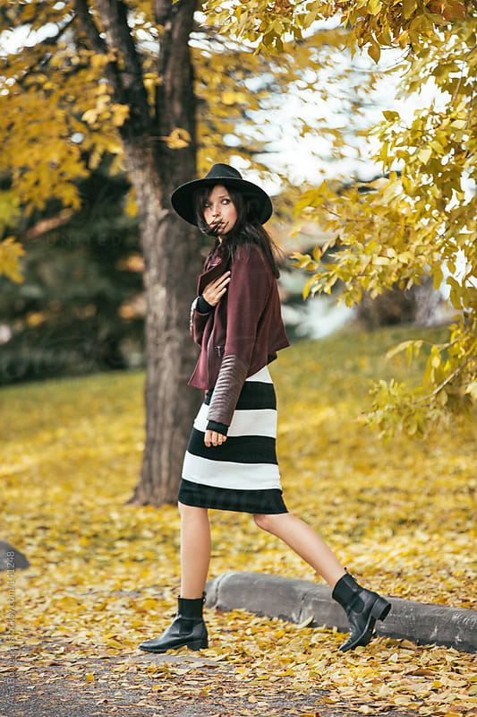 A well-dressed young woman walking away and looking over her shoulder by Ania Boniecka for Stocksy United