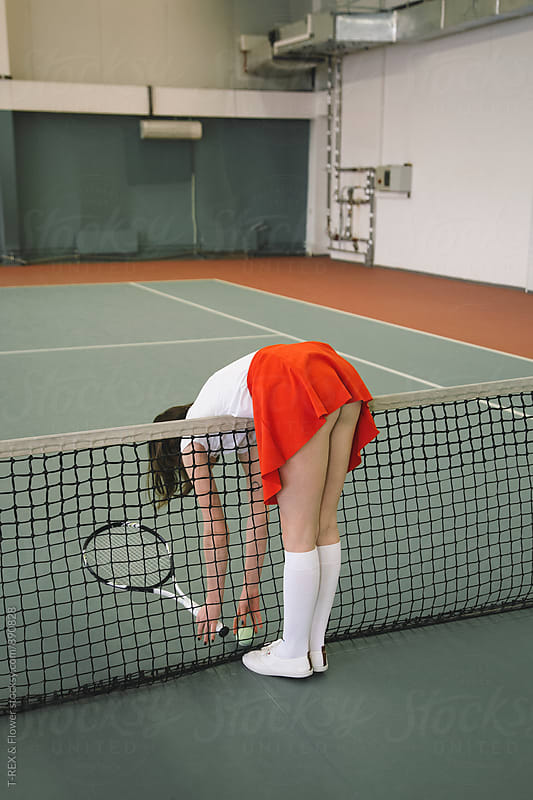 Back view of woman in red skirt picking up ball by Danil Nevsky for Stocksy United