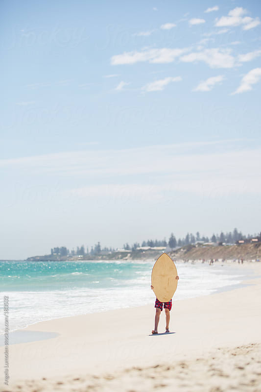 Child standing with skim board at the beach by Angela Lumsden for Stocksy United
