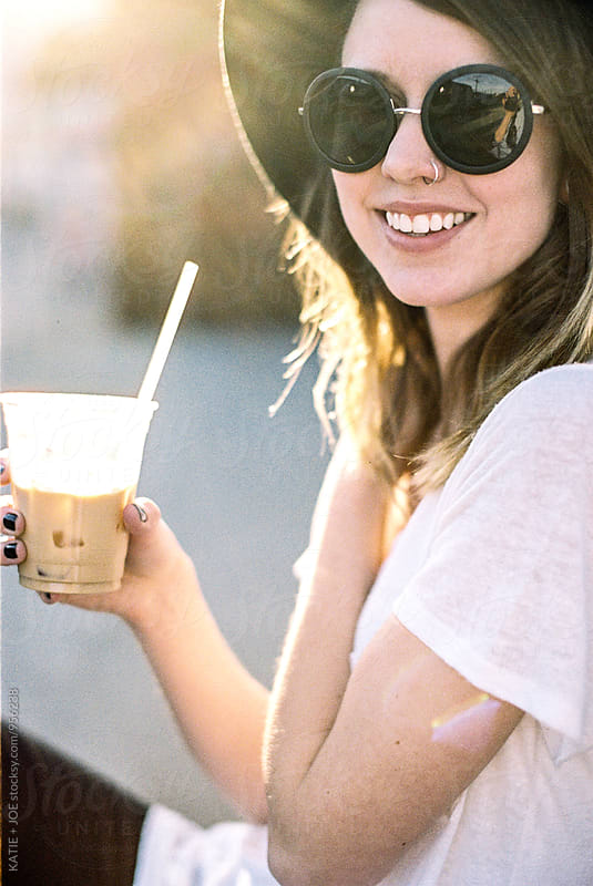 Woman wearing a hat and sunglasses holding a drink with a straw by KATIE + JOE for Stocksy United