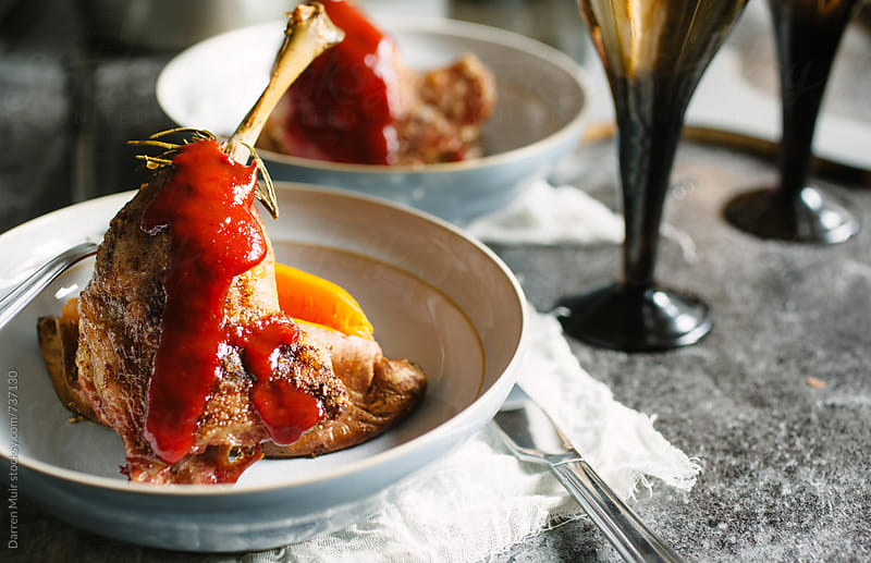 Roast duck leg with baked sweet potato and plum sauce. by Darren Muir for Stocksy United