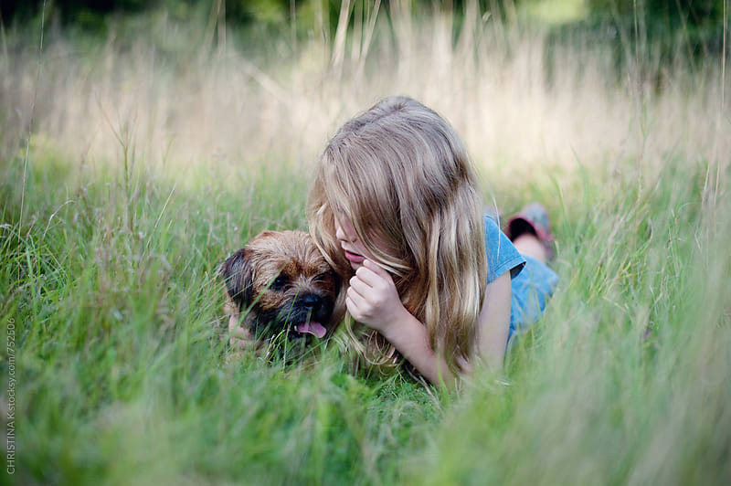 Girl laying in the grass with her dog by CHRISTINA K for Stocksy United