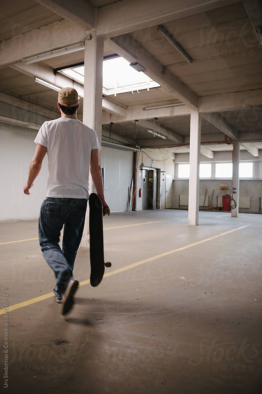 Back view of skateboarder in storehouse by Urs Siedentop & Co for Stocksy United