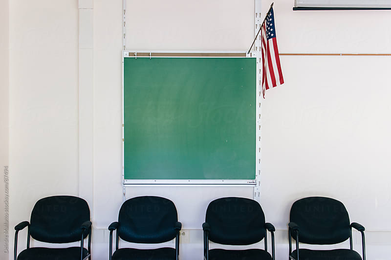 classroom with blackboard, chairs, and American flag by Deirdre Malfatto for Stocksy United