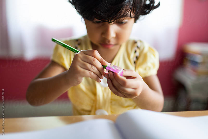 A little girl sharpens a pencil by Saptak Ganguly for Stocksy United