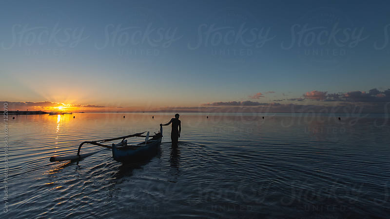 Man walking a canoe in Sanur, Bali by Gary Radler Photography for Stocksy United