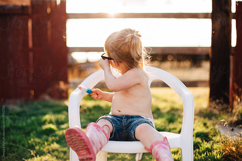 Toddler girl in chair with popsicle by Jessica Byrum for Stocksy United