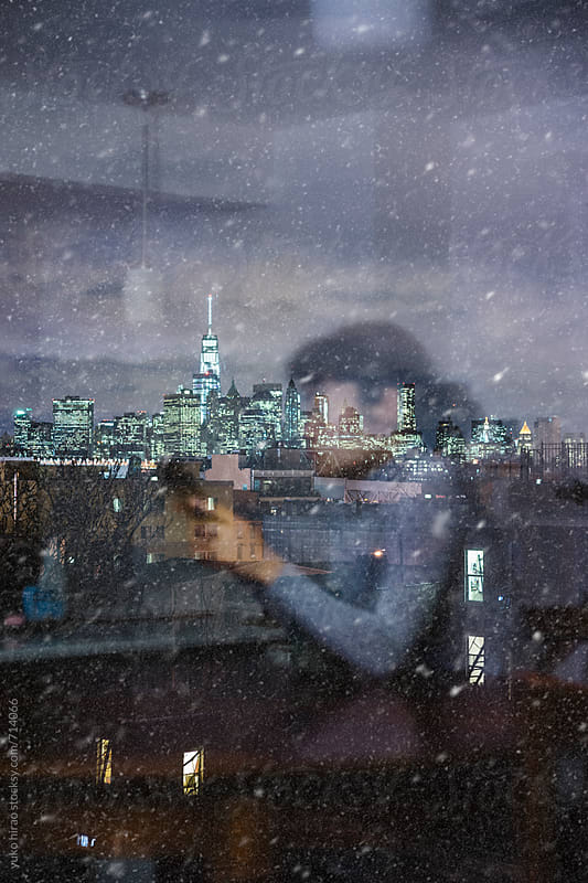 Urban living in winter - Relaxed woman at home and  illuminated Manhattan in snow by yuko hirao for Stocksy United