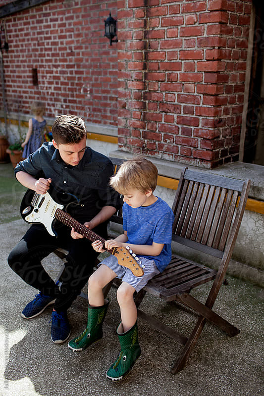 Teen boy teaches little brother to play guitar. by Julia Forsman for Stocksy United
