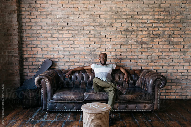 Black man looking at camera from a couch by Beatrix Boros for Stocksy United