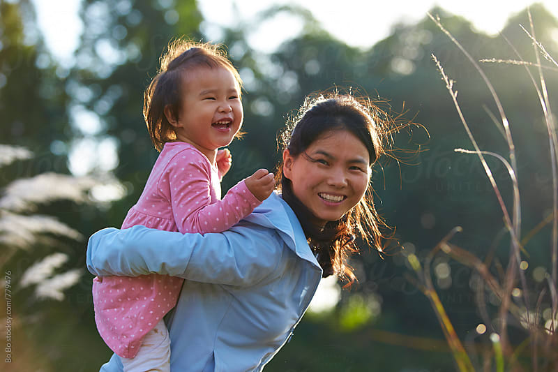 happy little asian girl outdoor with her mother  by Bo Bo for Stocksy United