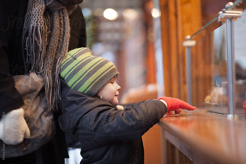 Boy buying sweets on Christmas market by Mima Foto for Stocksy United