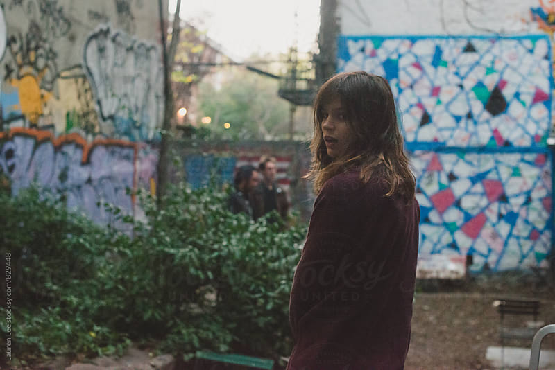Grainy portrait of young woman amid graffiti by Lauren Naefe for Stocksy United