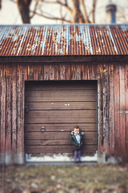 Toddler Girl Standing Against an Old Garage Door by Kevin Keller for Stocksy United