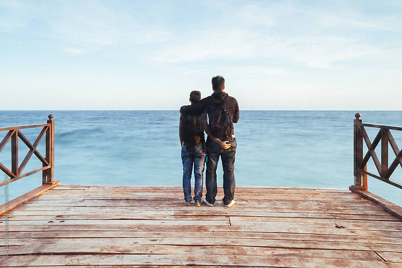 Couple embracing watching the sea by ACALU Studio for Stocksy United