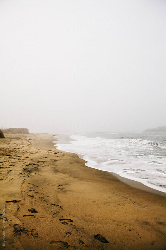 Misty waves on a beach with footprints by kkgas for Stocksy United