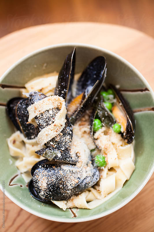 fresh tagliatelle with mussels, shallots, and peas by Christine Han for Stocksy United